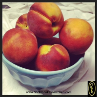 Fresh peaches in a blue bowl