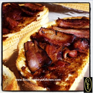 Divide bacon between two pieces of toast.